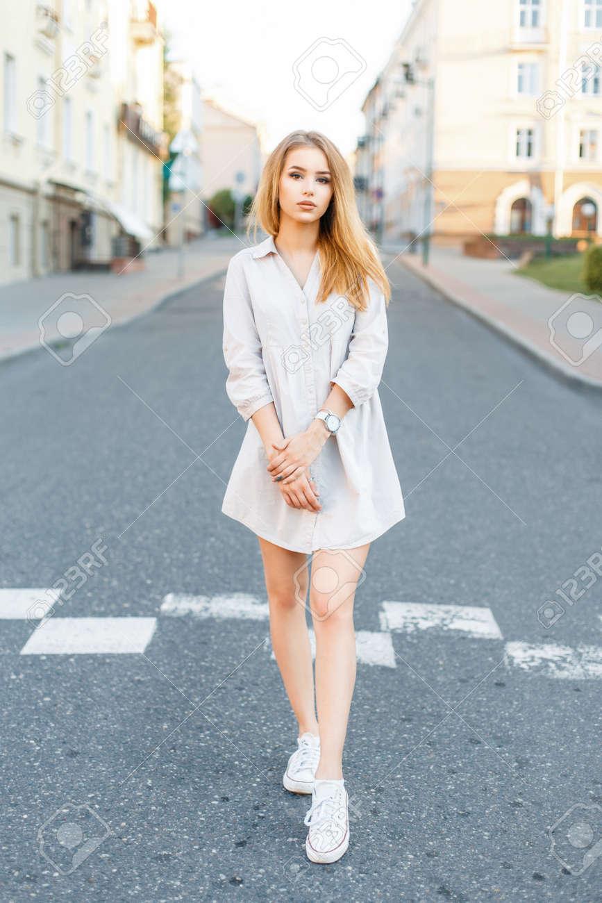dbd09ac4ef78 Archivio Fotografico - Giovane bella ragazza con vestiti alla moda che cammina  sulla strada sullo sfondo della città.