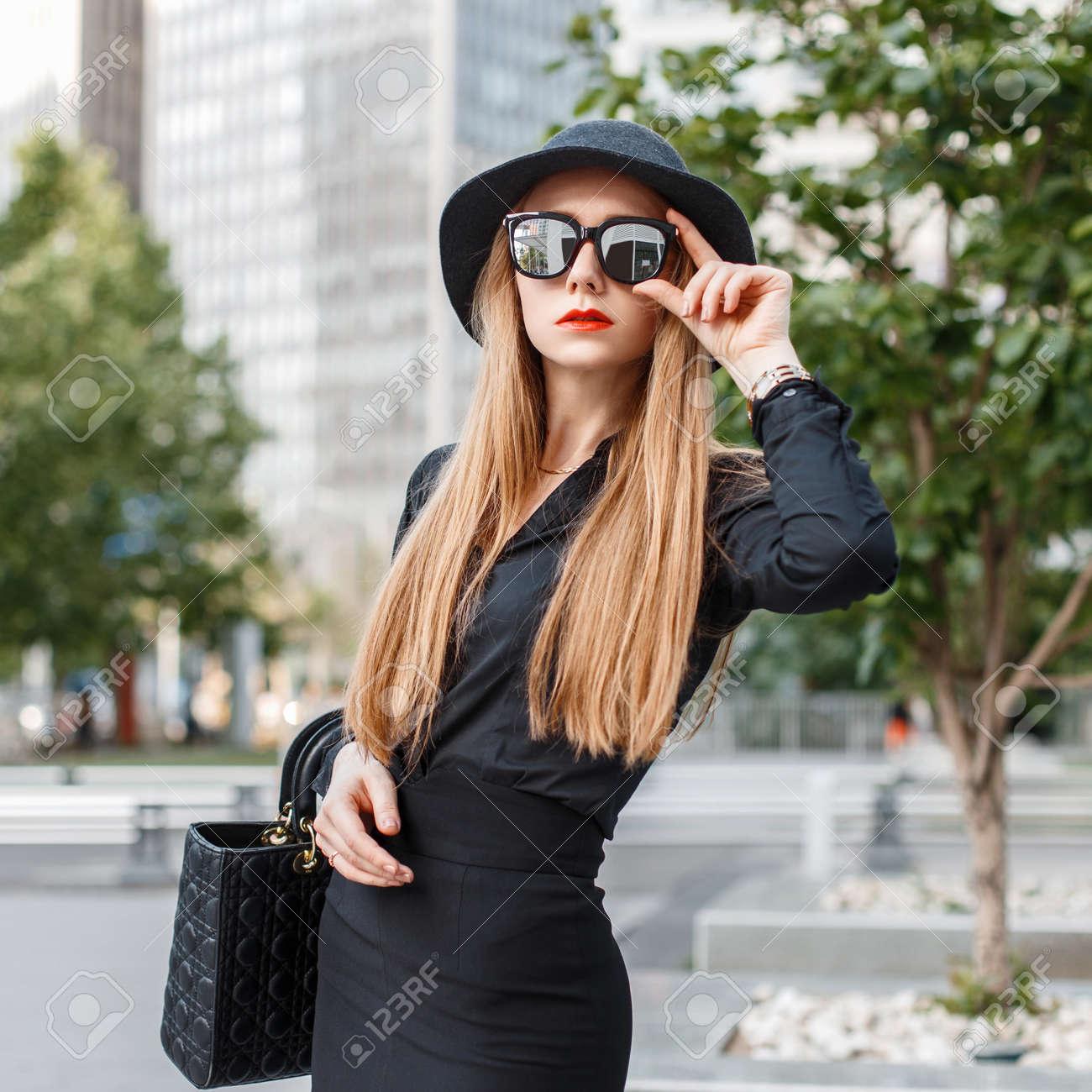 wholesale dealer 54f1d ace5b Bella ragazza alla moda in abiti neri con occhiali da sole e un cappello  sullo sfondo della città. Il concetto di una donna d'affari di successo.