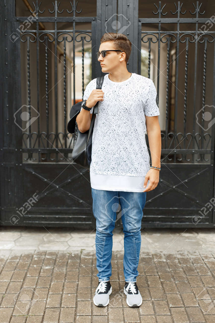 White t shirt and blue jeans - Stock Photo Young Handsome Hipster Man In A White T Shirt Blue Jeans And Sneakers Standing On The Street Backpack With A Cap On His Shoulder