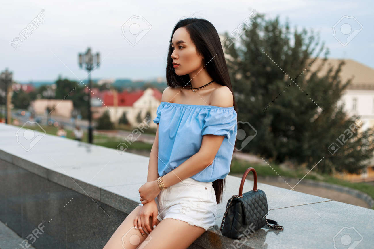 74f080032e Beautiful fashionable asian woman in a blue blouse and white shorts with a  bag sits on