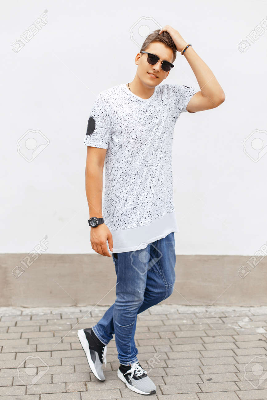 White t shirt and blue jeans - Stock Photo Young Handsome Man In A White T Shirt Blue Jeans And Sneakers Standing Near A White Wall