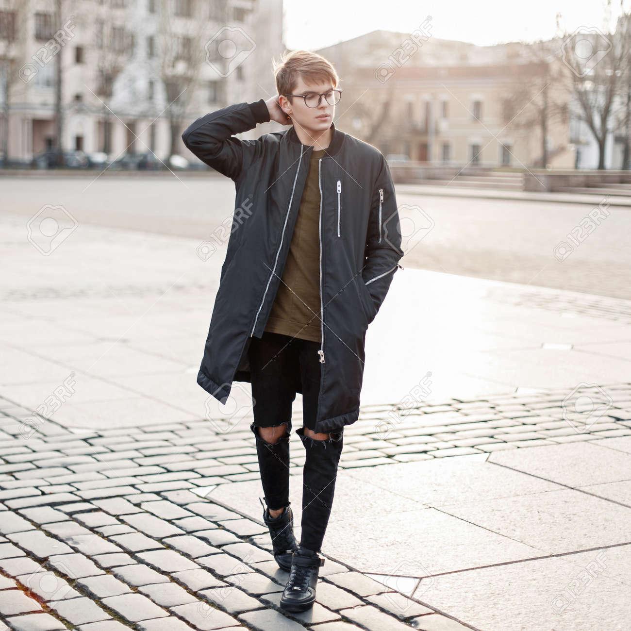 5c559ade0ed Banque d images - Beau jeune homme avec des lunettes dans une veste noire  en jeans déchirés et des chaussures noires traverse la ville