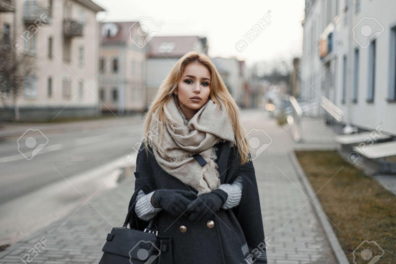 reputazione affidabile offrire sconti sulle immagini di piedi di Giovane donna in un cappotto con una sciarpa in città.