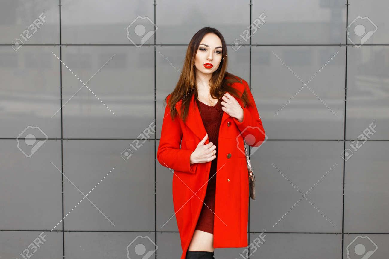 27dc227339febe Schöne stilvolle Frau in einem modischen roten Mantel posiert in der Nähe  einer grauen Wand Standard