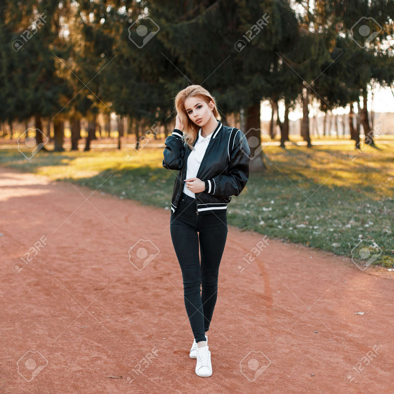 9a264e463b80 Photo beautiful woman in a black jacket black jeans and white shoes in the  park on