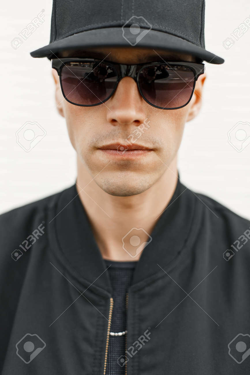 Portrait of a young handsome guy wearing black glasses and a baseball cap  Stock Photo - 6260b36c6f4