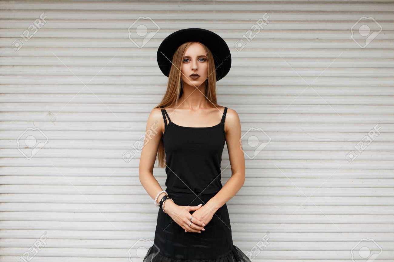Beautiful young girl in a trendy black hat and stylish black clothes near a  white wall b206c4e2206