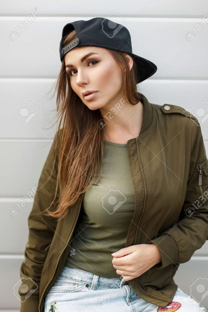 9df607265d Beautiful young woman with a baseball cap in a green military jacket and a  T-
