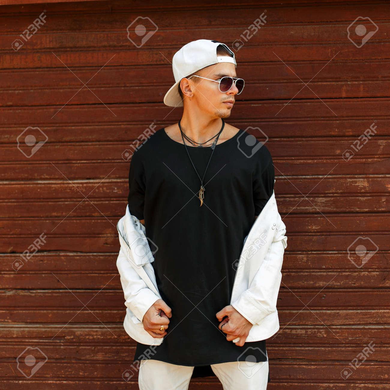 d19039abad47 Hombre guapo de moda en una camiseta negra con una gorra de béisbol blanca  y gafas de sol posando cerca de una pared de madera