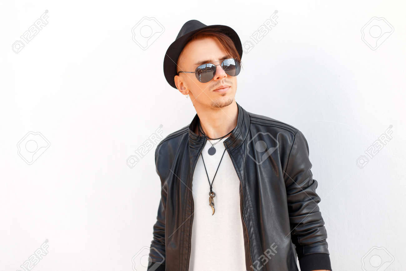 c2258b1f Stock Photo - Stylish handsome young man in a black hat with sunglasses in fashion  black jacket posing on white background
