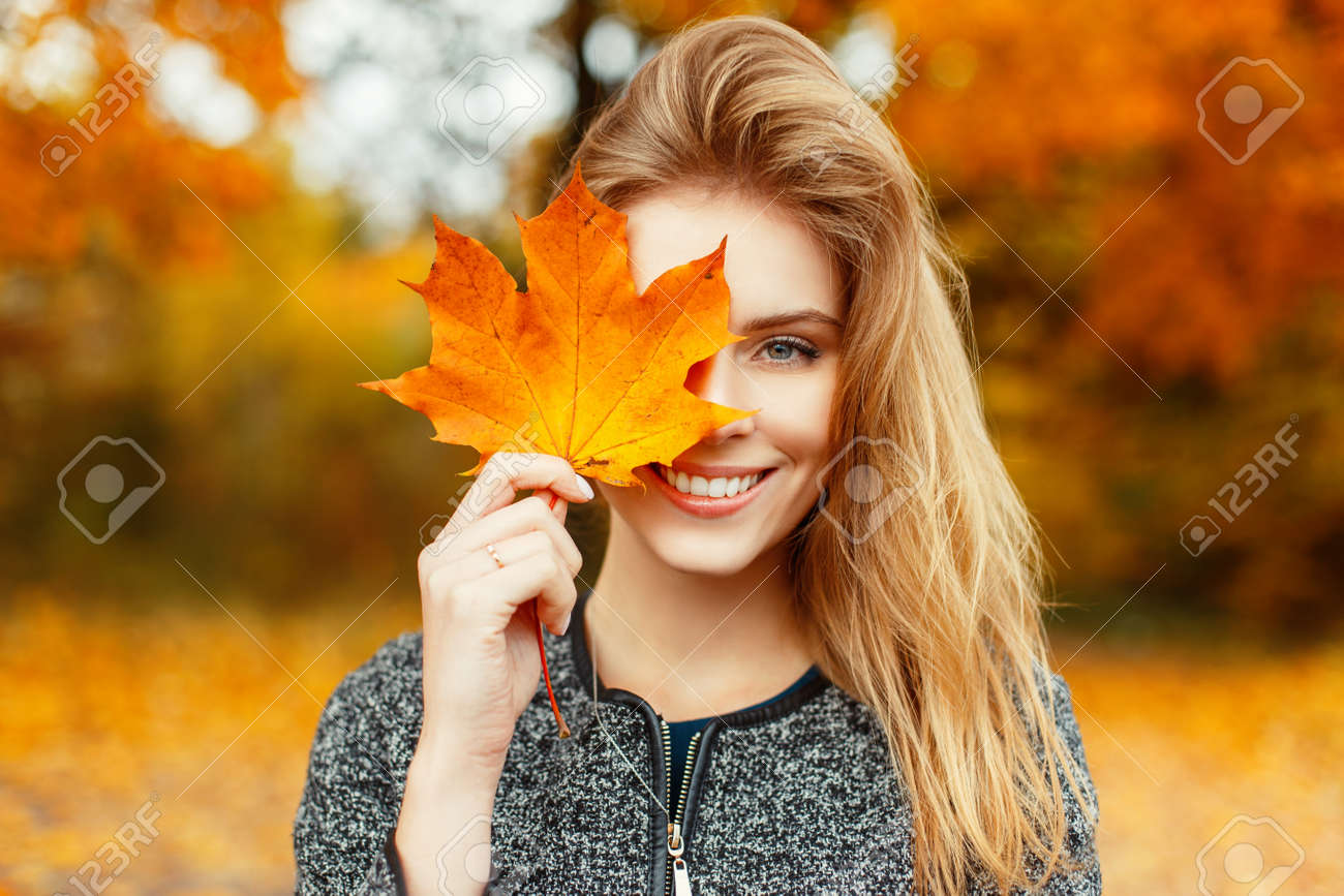 Beautiful happy woman with a smile holds an autumn yellow leaf near the face - 90921795