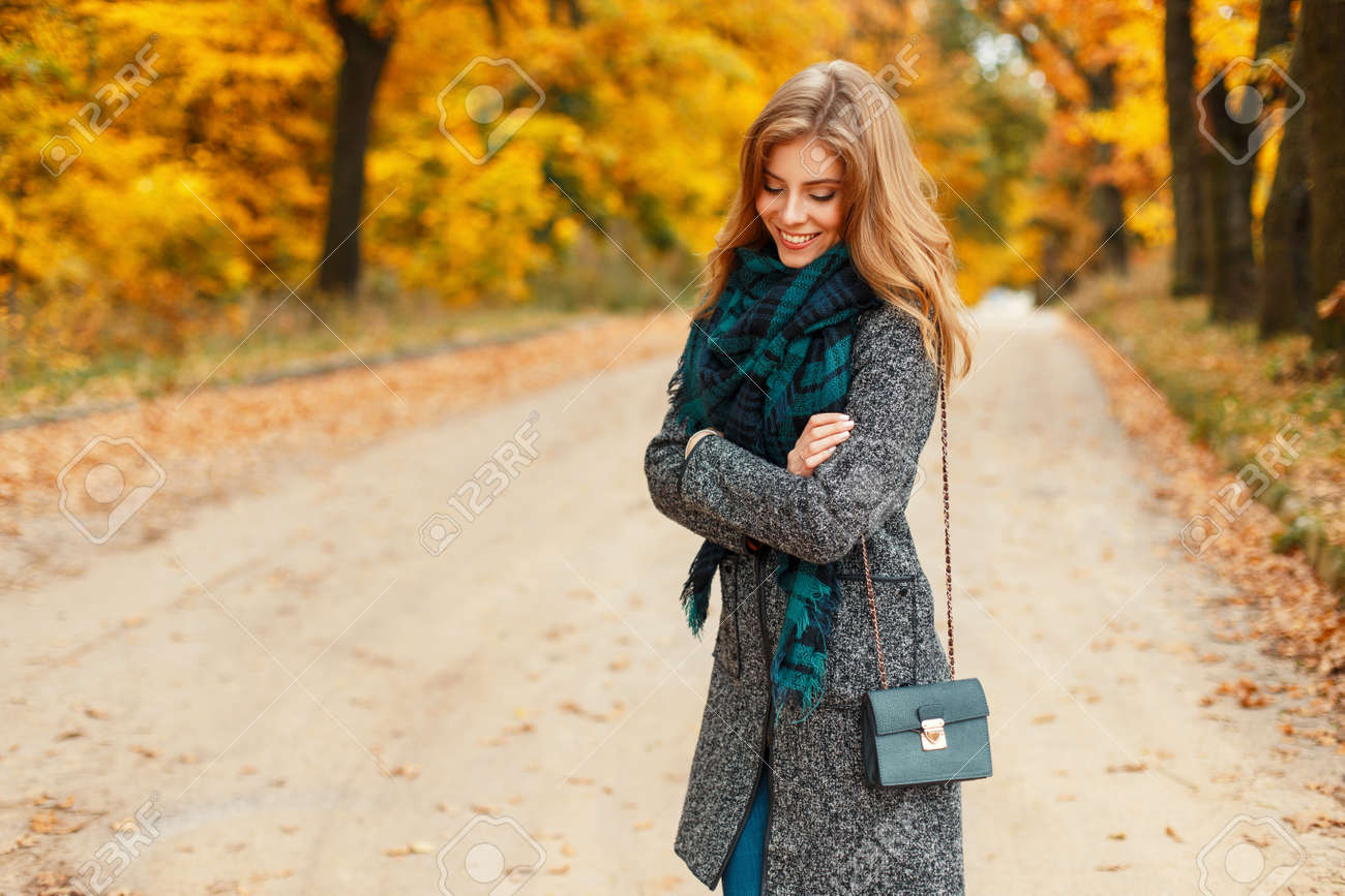 78c21dca9b Happy beautiful young woman with a smile in stylish clothes with a scarf  posing in an