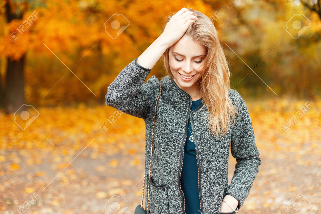 36c16555d7 Beautiful young happy woman in fashionable autumn clothes walking in a park  with yellow foliage Stock