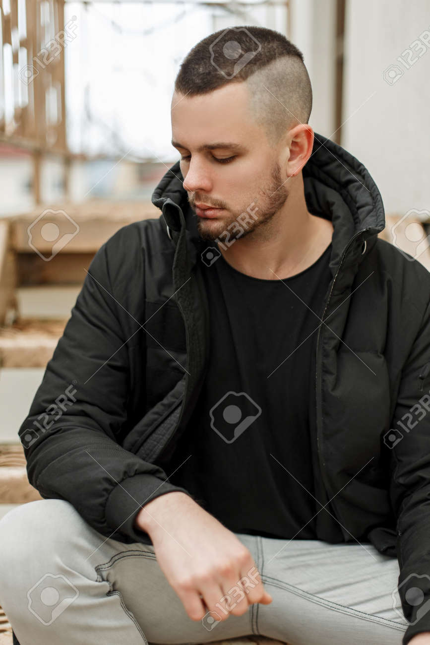 37f0b18b4624 Handsome young man with a short hairstyle in a black winter jacket sits on  the street