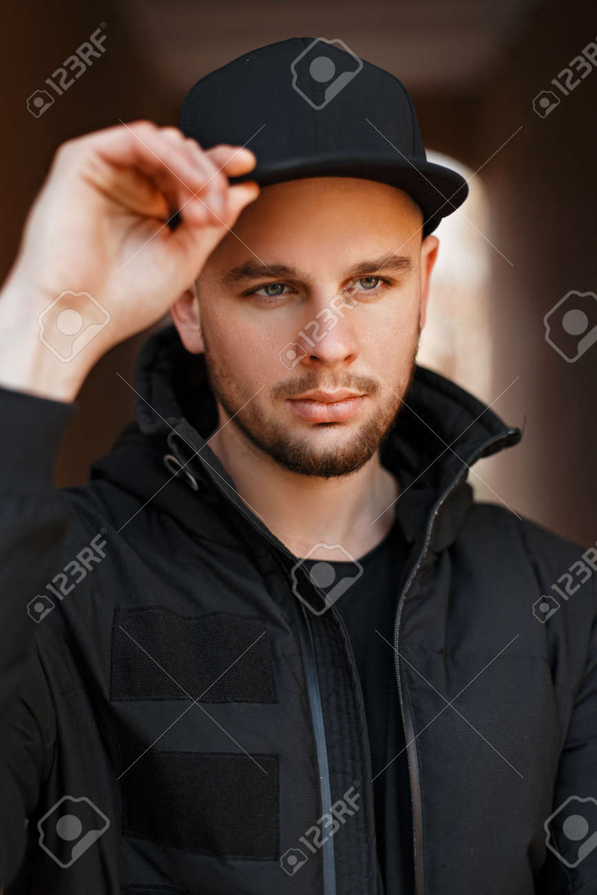 91a116fd37f Stock Photo - Street portrait of a handsome young man in a black stylish  baseball cap and winter jacket