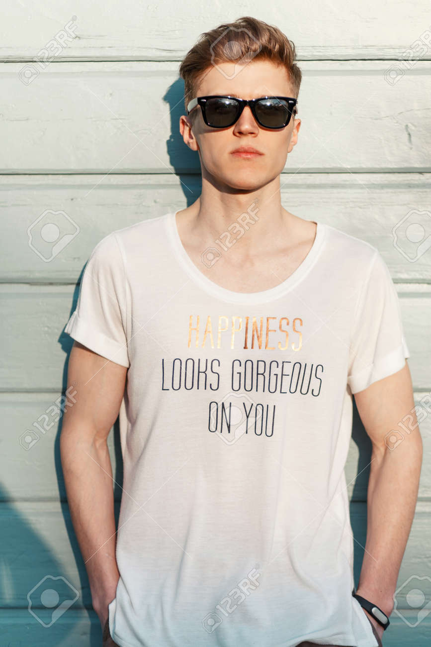 f4fea6ff8 Handsome hipster guy with sunglasses in a white T-shirt and an inscription