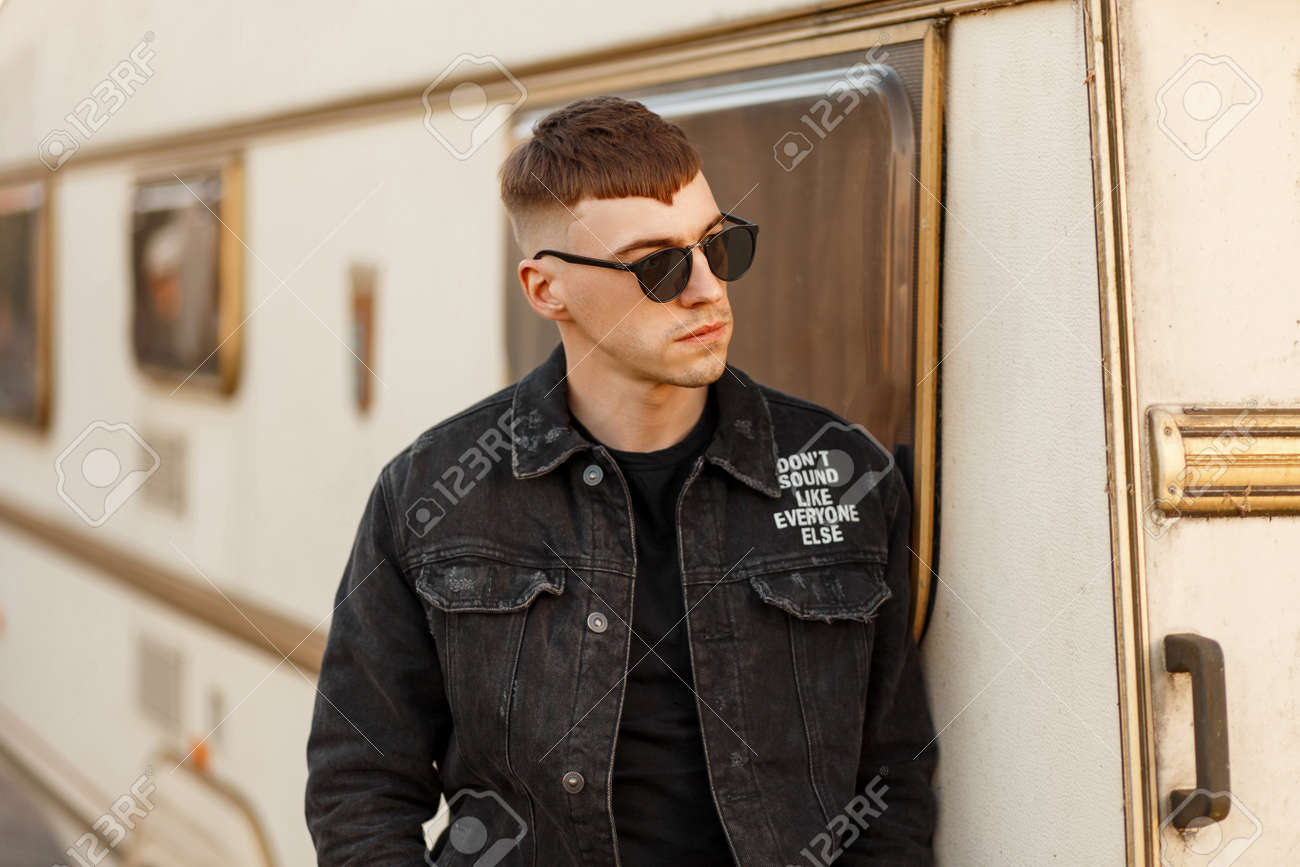Fashion Handsome Young Guy In Sunglasses In A Black Denim Jacket