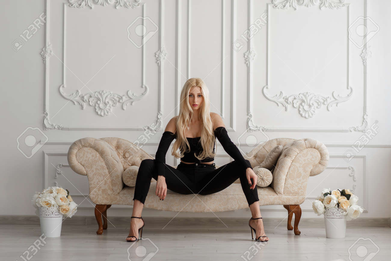 Sexy beautiful young model woman in fashionable black clothes with jeans sitting on a sofa in a vintage room - 111458563