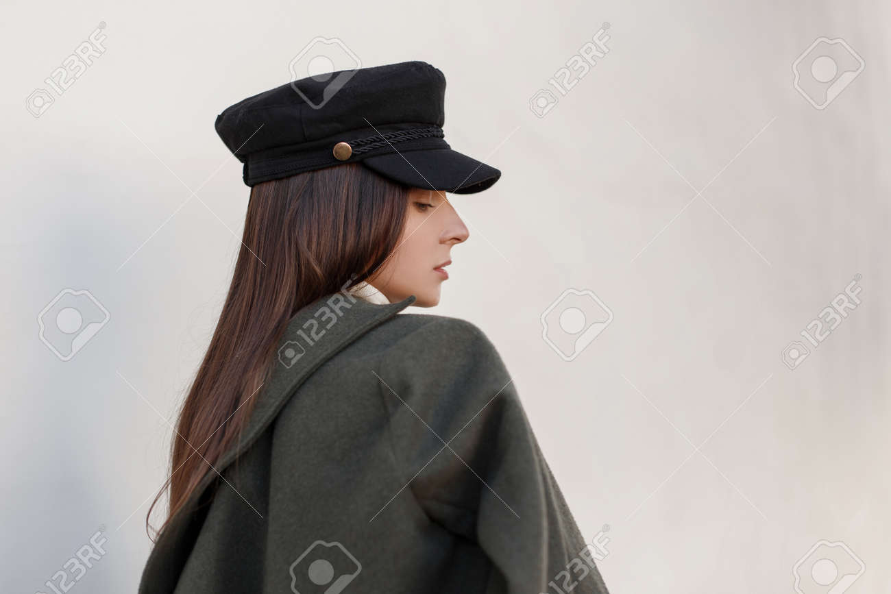 ecafa5833a Fashionable beautiful young woman in a hat and a stylish green coat near  the wall Stok