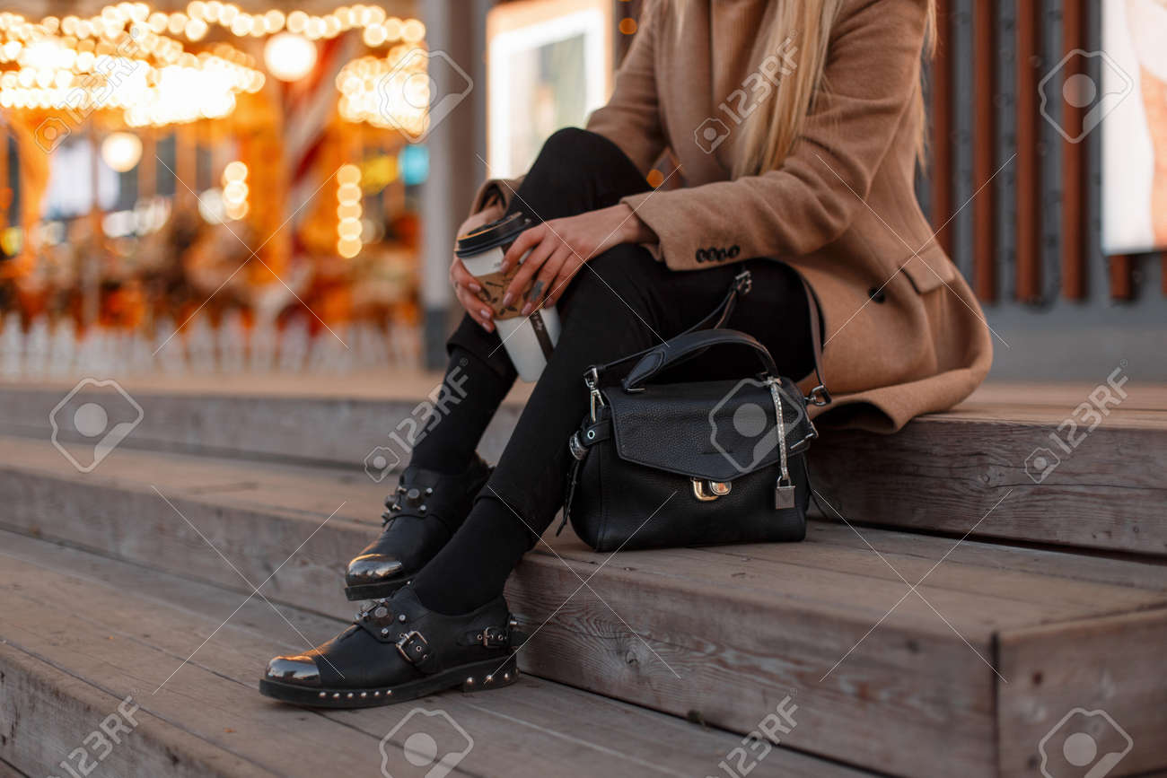 Young girl in a vintage coat with a warm knitted sweater, stylish jeans, black leather fashionable modern shoes and a stylish leather bag sits with a cup of coffee. Women's stylish clothing. Close-up - 112760418