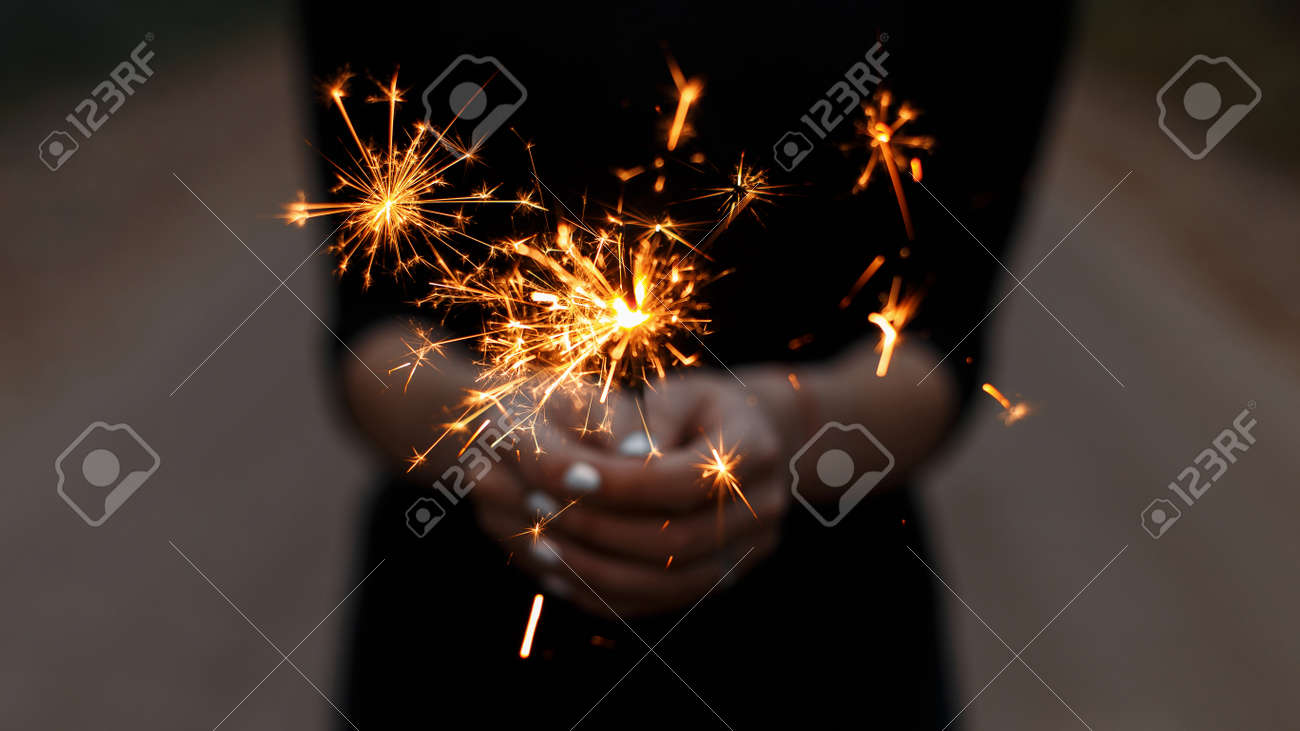 Amazing festive sparklers in the hands of a young woman. Girl celebrates happy birthday. Bright orange sparks with a close up. - 119101696