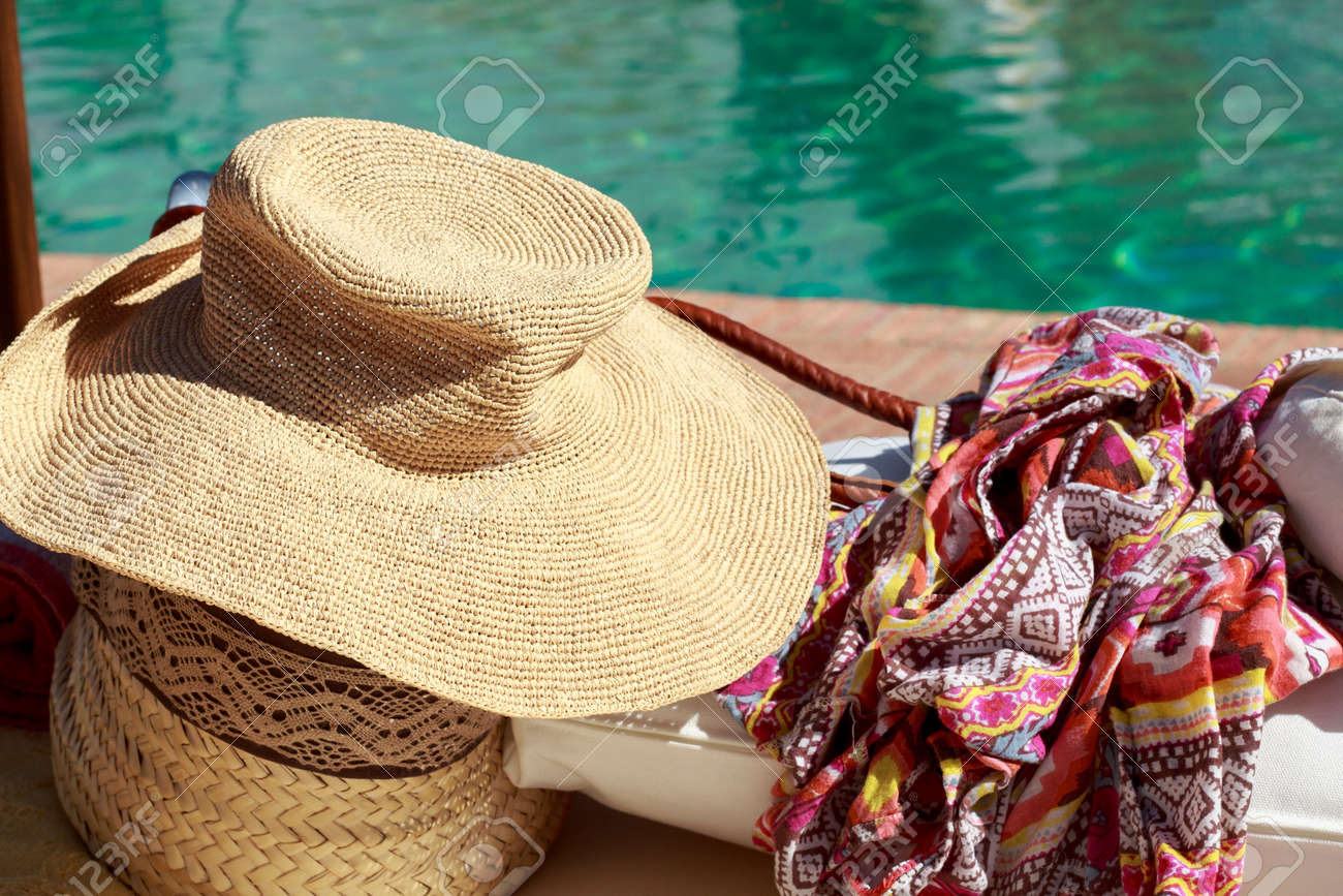 f99cb7fba Sun hat and pareo in front of a swimming pool