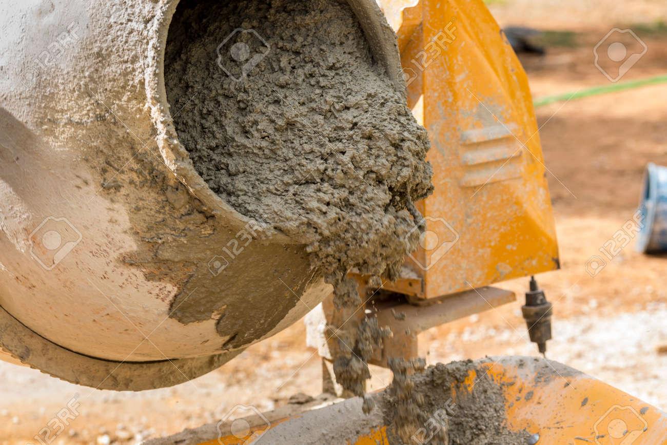 verter el mortero de la mezcladora de cemento en una carretilla obras de construccin foto
