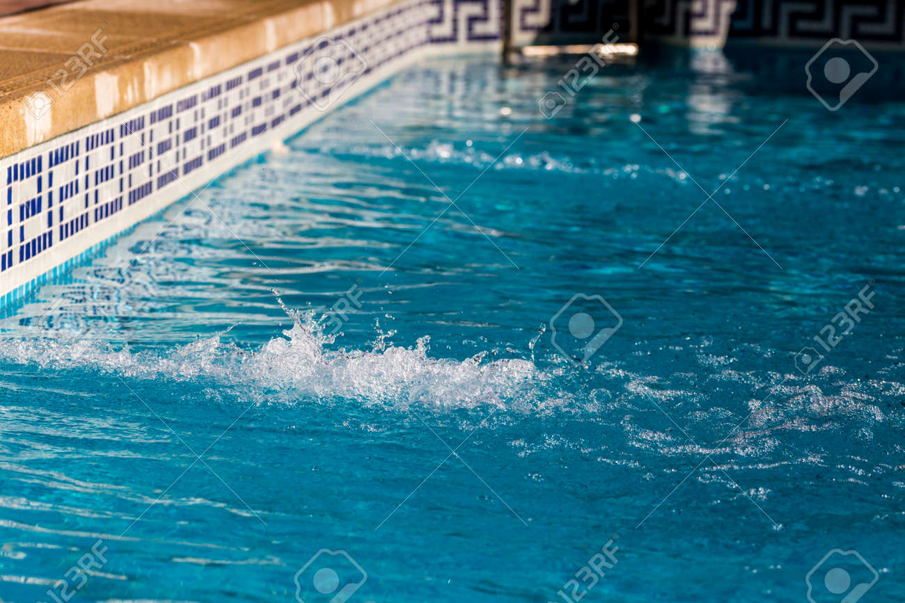 Water jets of a swimming pool with blue tiles