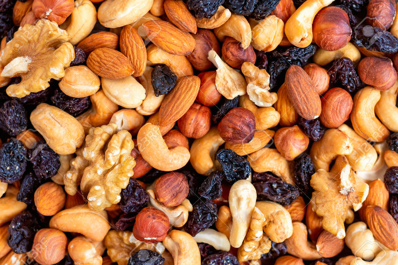 Background and pattern of a mix of different nuts and raisins. The concept of healthy and proper nutrition. Source of vitamins, trace elements, vegetable proteins and fats, oils. Health care - 165392454