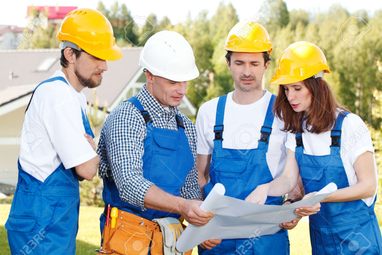 Team of builders in hardhats with blueprint outdoors stock photo stock photo team of builders in hardhats with blueprint outdoors malvernweather Image collections