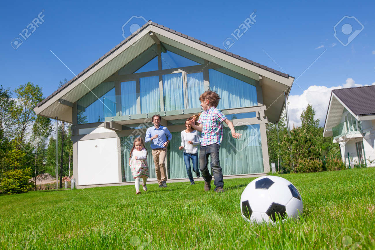 Family with children playing football on the backyard lawn near their house - 121683554