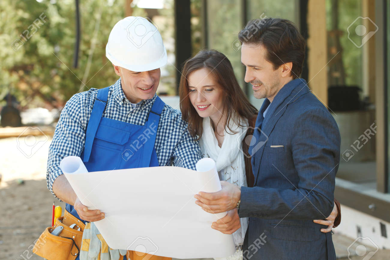 Foreman shows house design plans to a young couple at construction site outdoors - 134043506