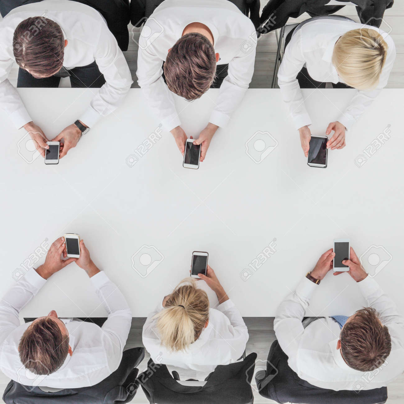 Business people using smartphones sitting at table in office, white copy space background - 141289669