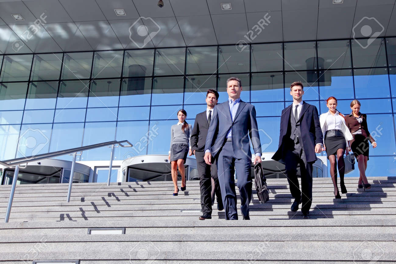 Group of business people and their leader walking down stairs outside office building successul deal negotiation concept - 141711111