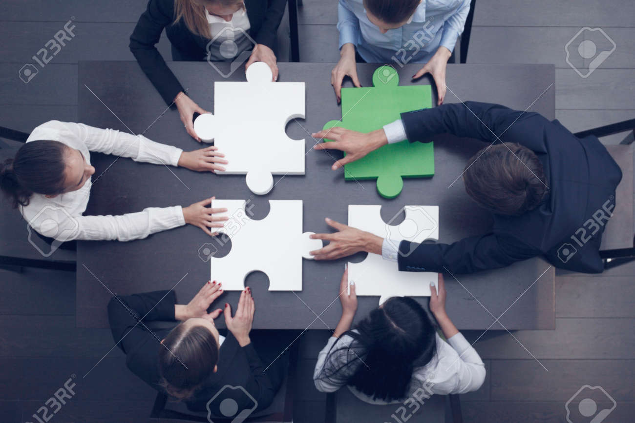 Group of business people assembling jigsaw puzzle at office table, top view, team support and help concept, green and white pieces - 159097277