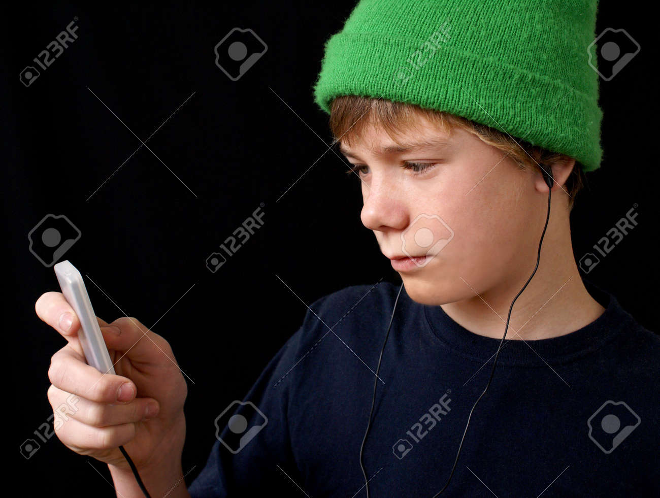 A teen boy listens to his mp3 player. Stock Photo - 4034666