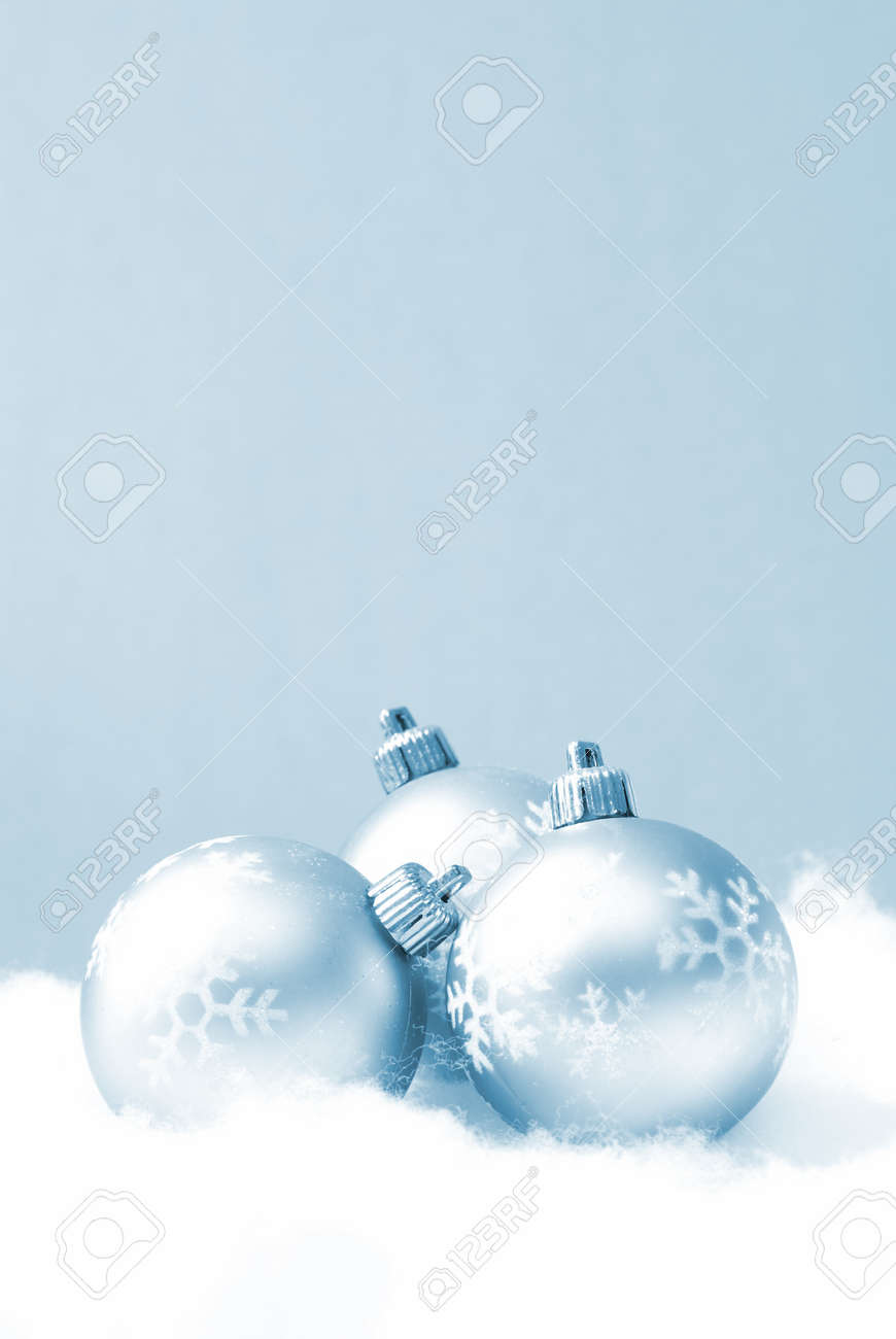 Three holiday baubles on some fake snow and coloured in blue monochrome. Stock Photo - 7754062