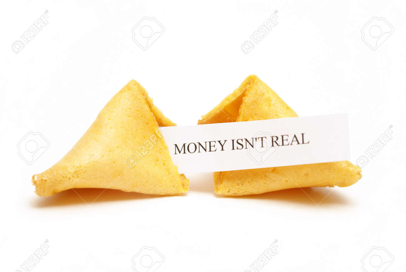 A cracked open fortune cookie stating that money isn't real. Stock Photo - 9909946