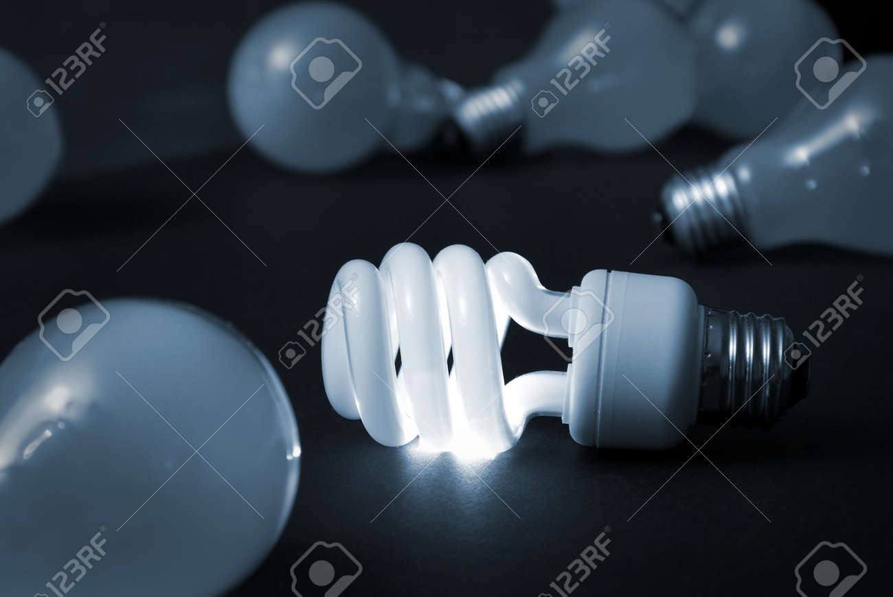 A new energy efficient CFL light bulb shines while the old ones fade into darkness. Stock Photo - 9909981