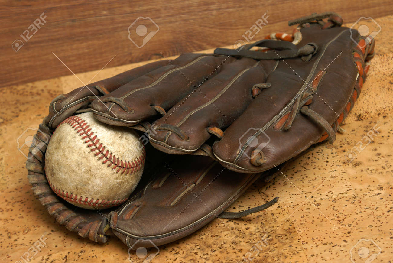 A low contrast image of a well used hardball and glove for those who love the sport of baseball. Stock Photo - 12365476