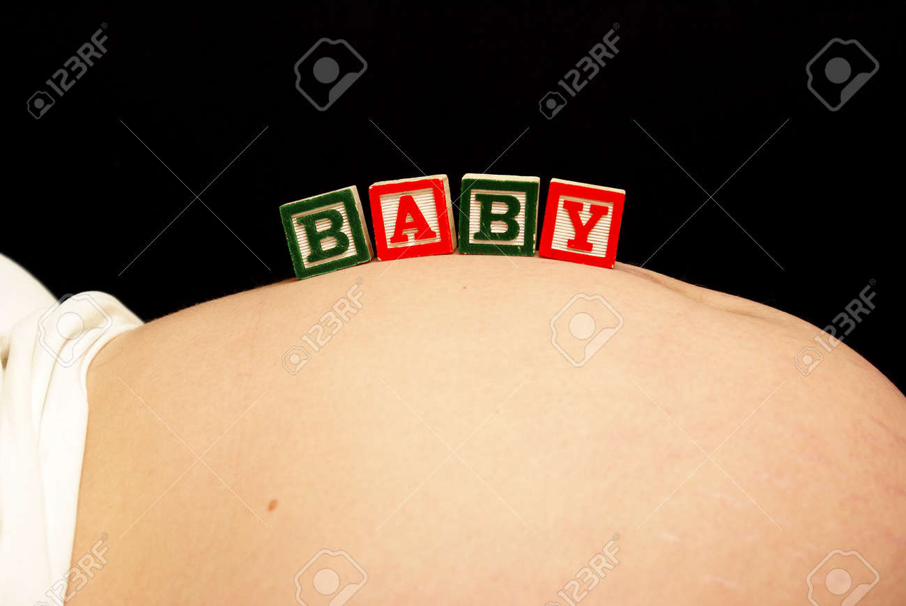 An expecting mother rests baby blocks on her pregnant belly. Stock Photo - 12687028