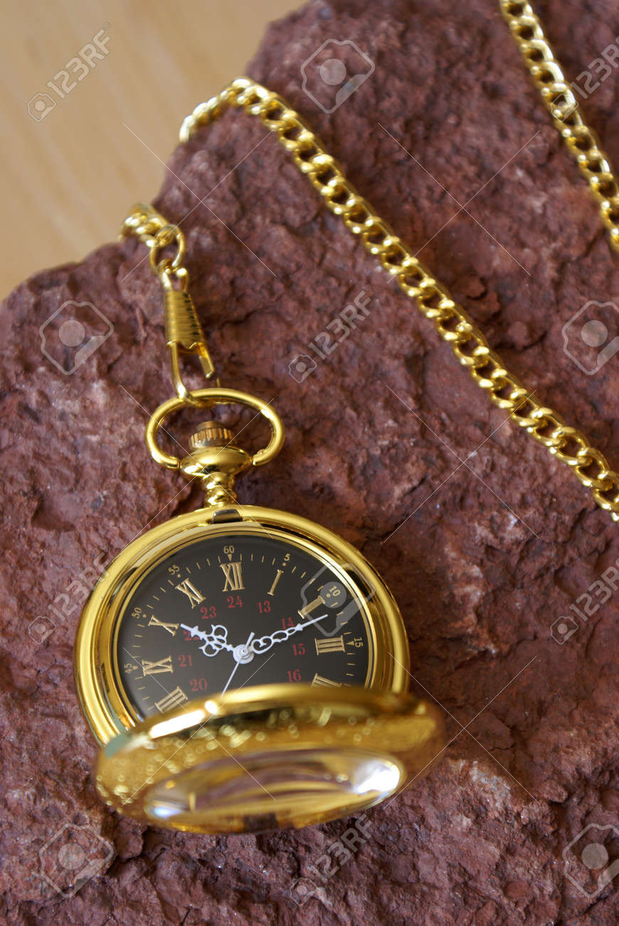 A gold pocket watch on a red sandstone. Stock Photo - 15716404