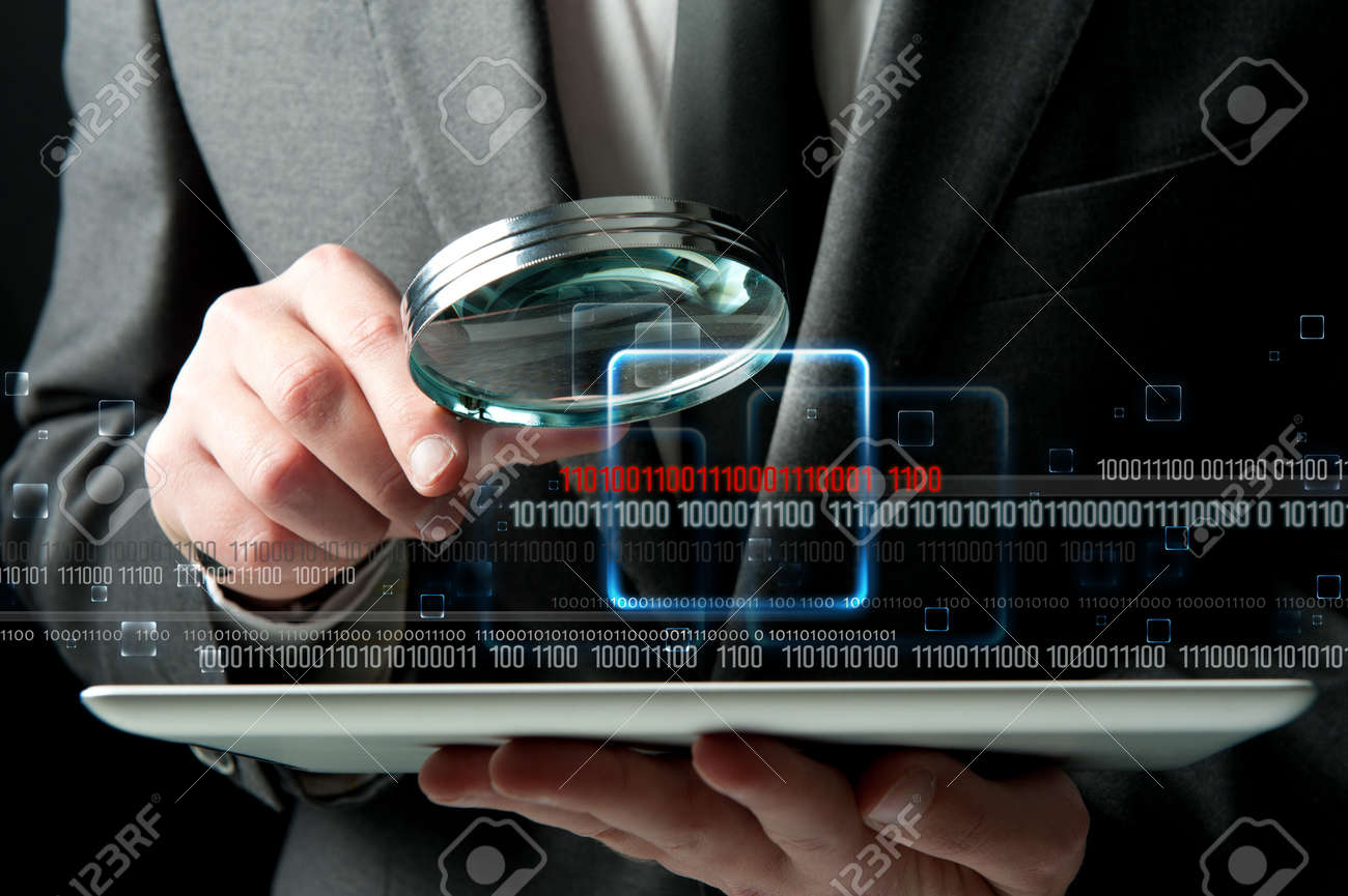 Businessman looks for the malicious code of a virus Stock Photo - 13196908