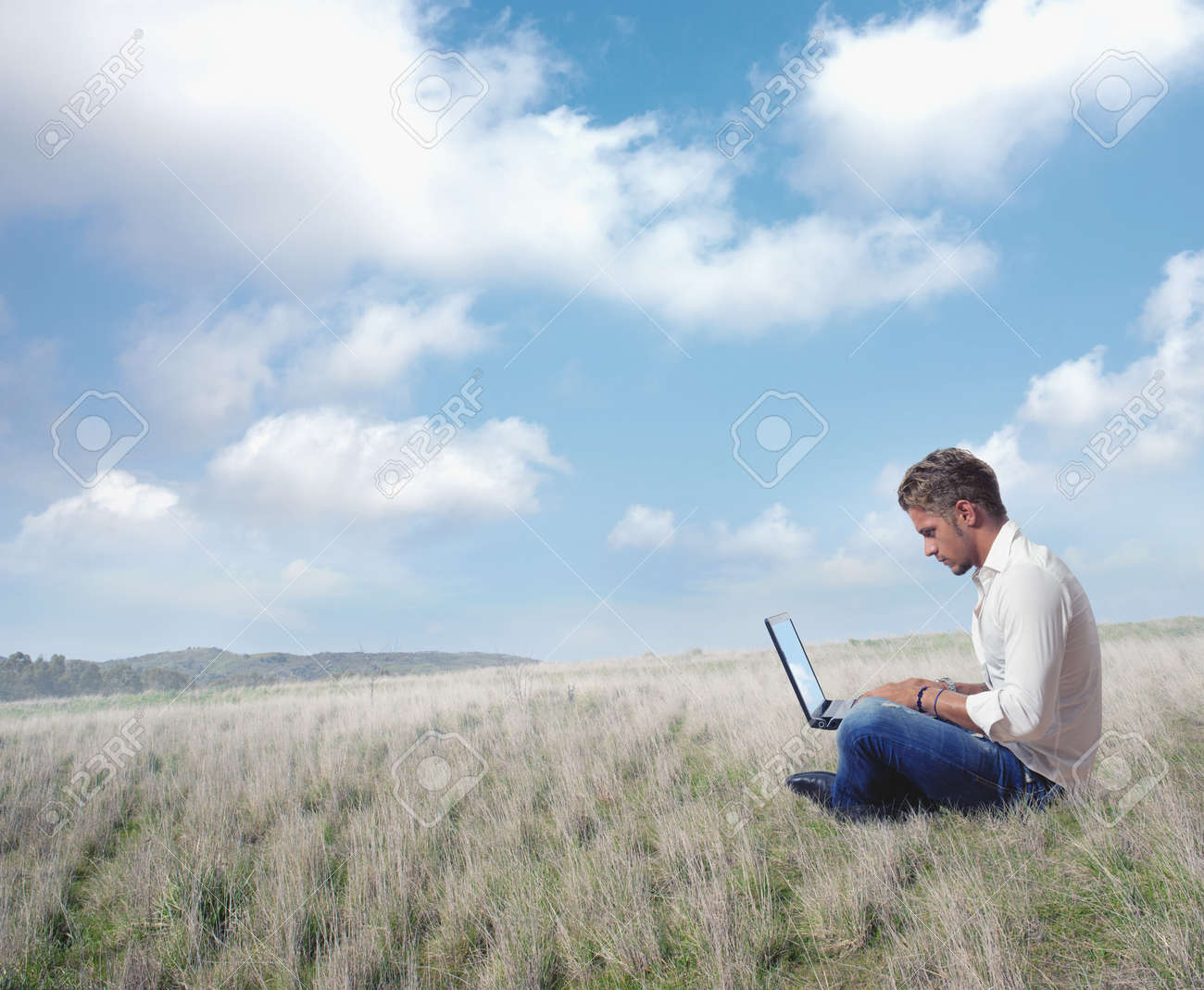 Boy works in a field with laptop Stock Photo - 15733849