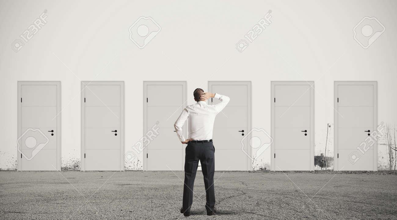 Concept of businessman choosing the right door - 20411738