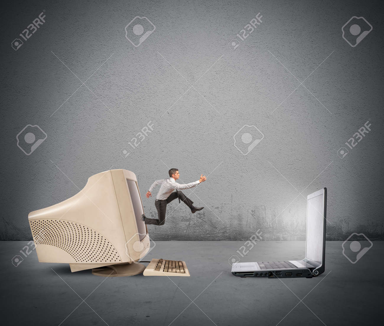 Businessman jumping from old computer to new laptop - 29767460