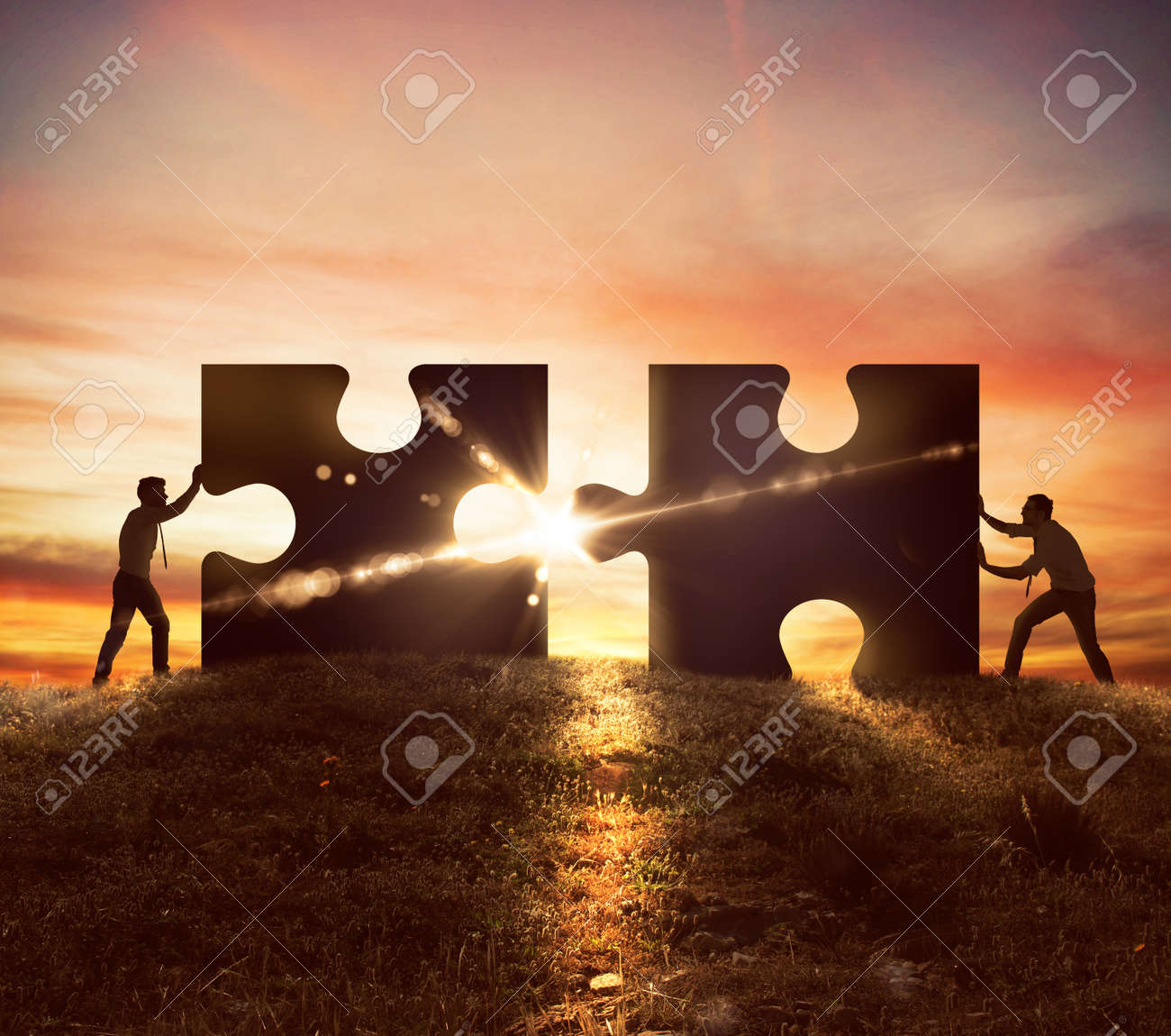 Men push two puzzle pieces at sunset Standard-Bild - 57764667