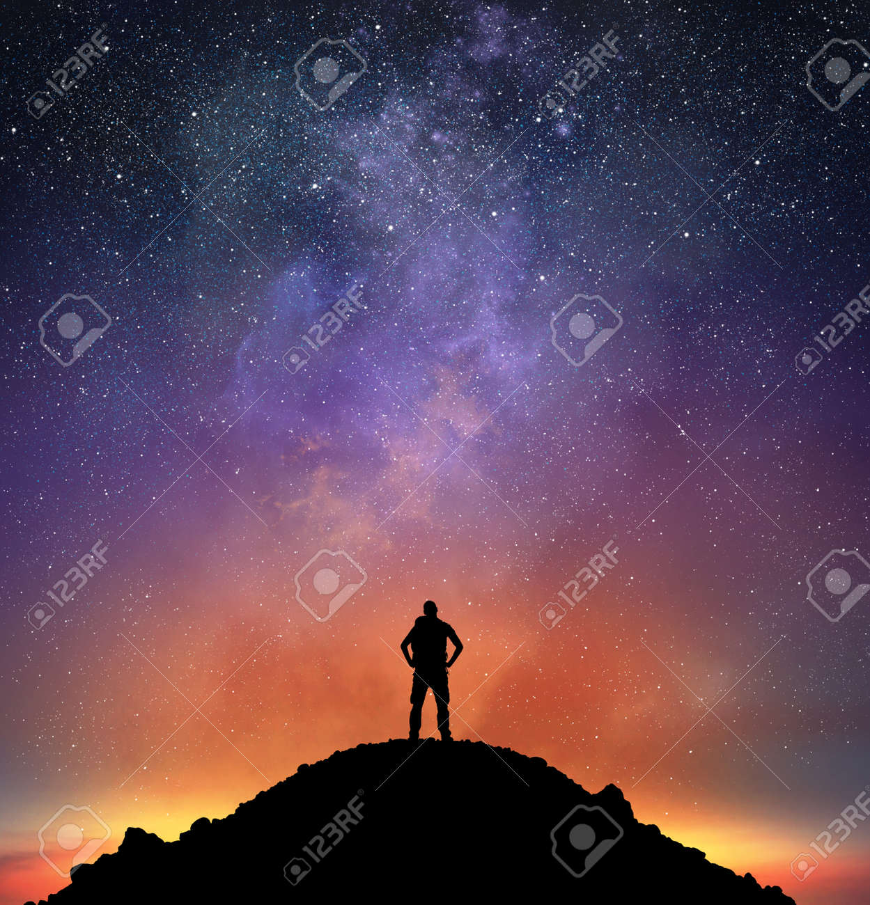 Excursionist on a mountain observe a bright sky full of stars Standard-Bild - 62101415