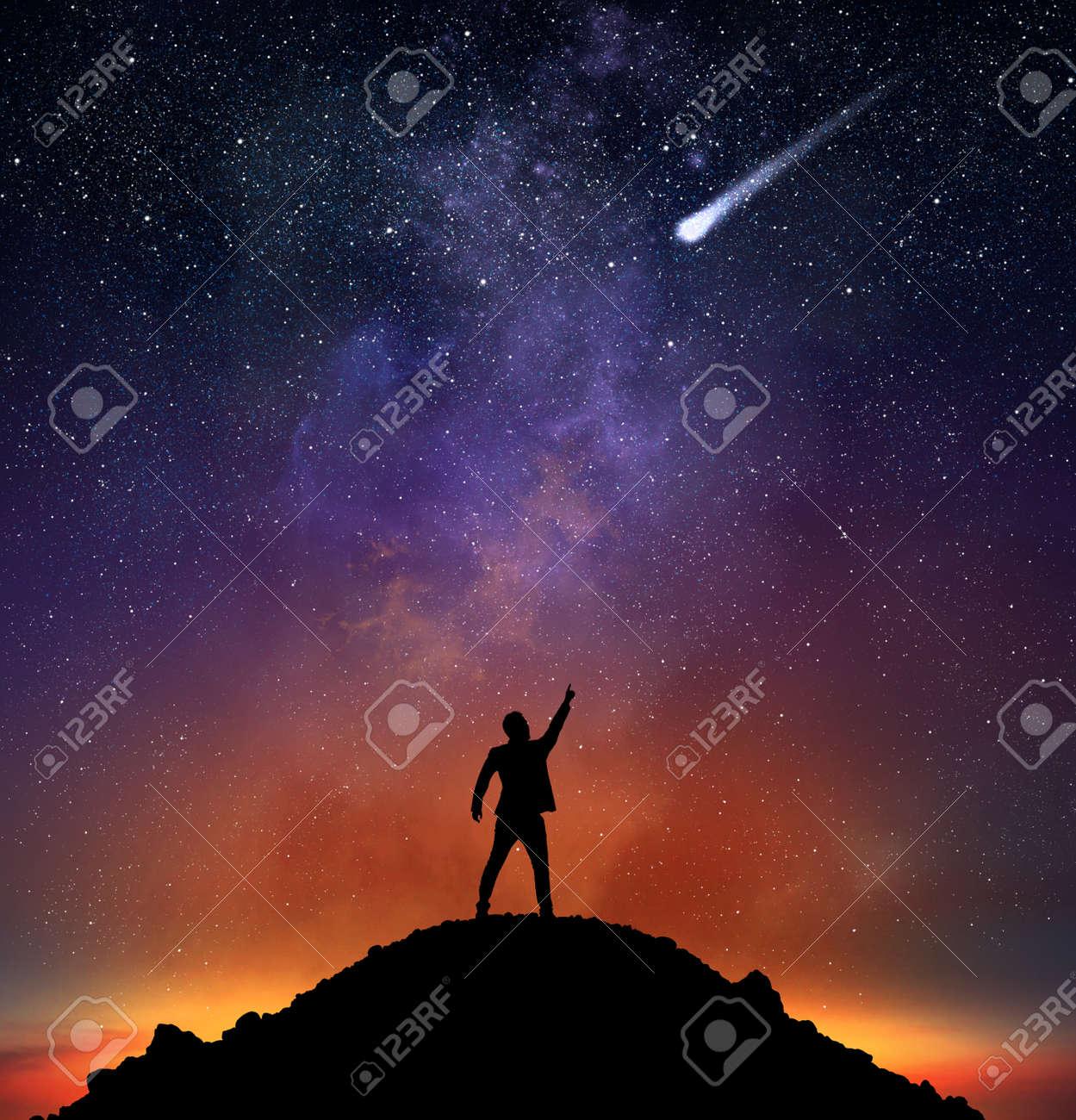 Businessman on a mountain indicate a falling star Standard-Bild - 62101419