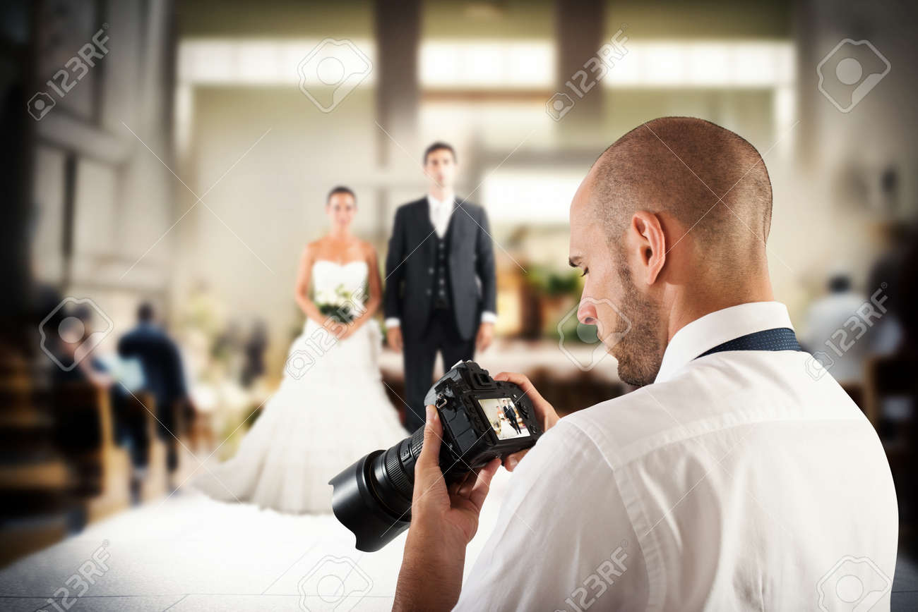 Photographer looks at the screen of camera to a wedding Standard-Bild - 62101438